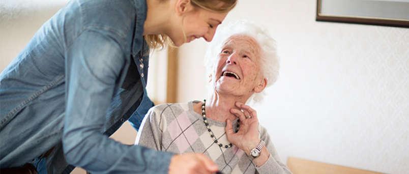 Caregiver laughing with senior
