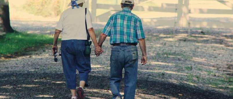 senior lady and senior man walking holding hands