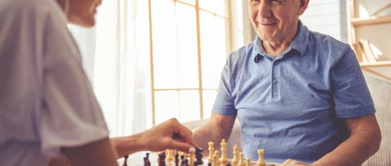 caregiver and senior playing chess