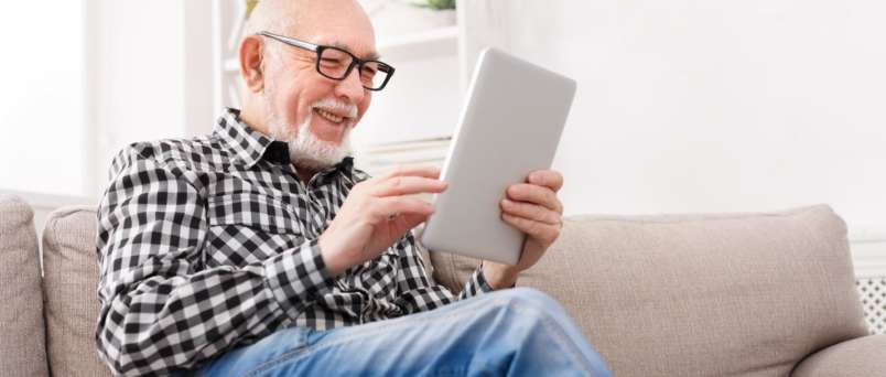 an elderly man using an ipad