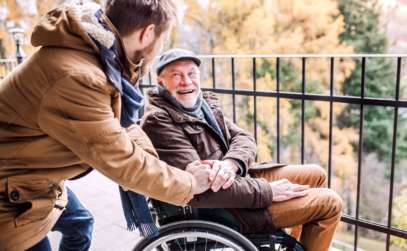 a caregiver assisting an elderly man in a wheelchair