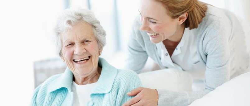 caregiver and senior sharing a laugh