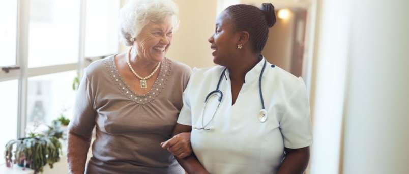 a caregiver and senior sharing a laugh arm in arm