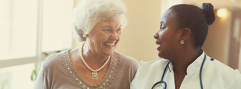 senior lady and caregiver sharing a laugh