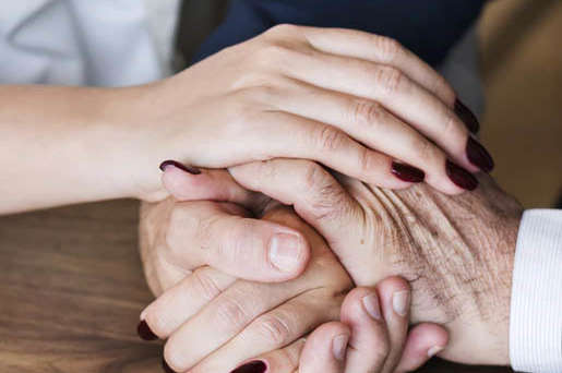 Senior and caregiver hands over top of each other