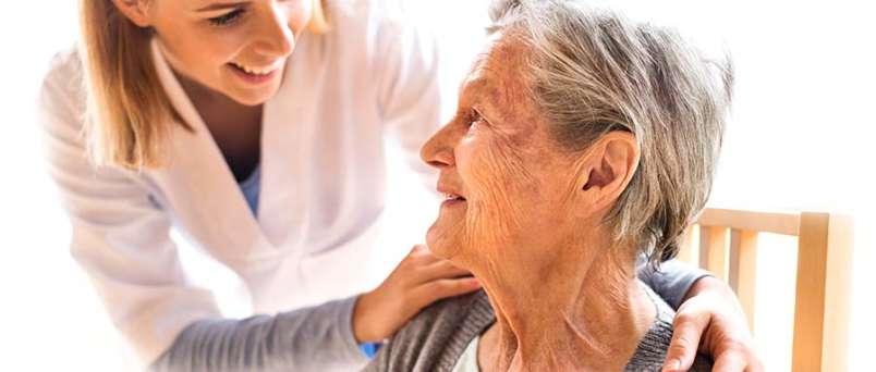 Caregiver placing arms around a seated senior