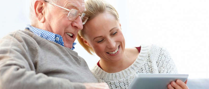 caregiver helping senior use a computer