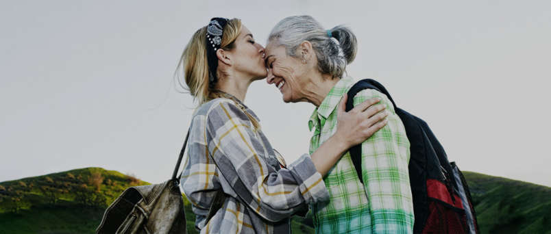 young woman kissing the forehead of senior woman