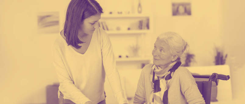 caregiver talking with elderly lady in a wheelchair