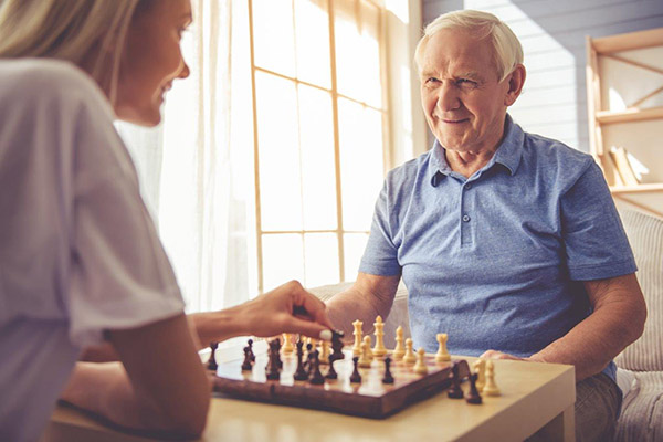 a caregiver and elderly man playing chess