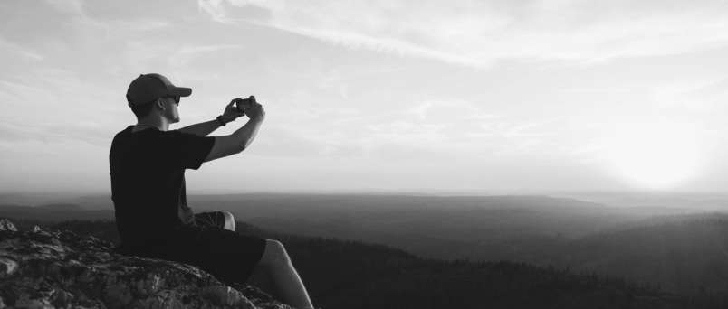 a man taking a picture of the landscape on top of a mountain