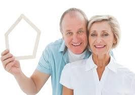 an elderly couple holding Popsicle sticks in the shape of a house