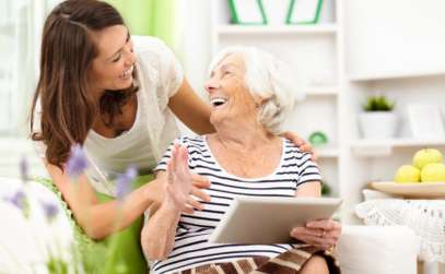 a caregiver laughing with a senior woman while she holds an ipad