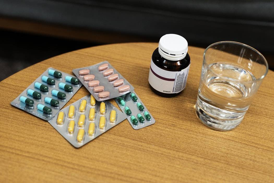 a table full of pills in their package with a glass of water