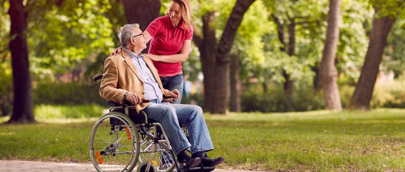 a woman helping an elderly man in a wheelchair