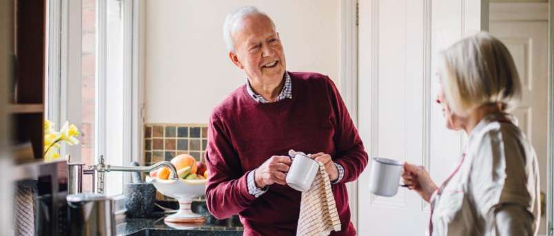 an elderly couple holding coffee mugs in a kitchen